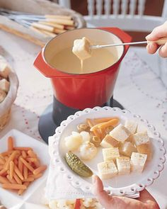 Cheese Fondue- Martha Stewart: 1 clove garlic; 1 1/2 cups apple cider or dry white wine; 8 ounces Gruyere cheese, grated (3 cups);  8 ounces Emmental cheese, grated (3 cups); 8 ounces raclette cheese, grated (3 cups); 2 tbsps lemon juice; 2 tbsps cornstarch; nutmeg; white pepper; 1 loaf French bread, Assorted pickled vegetables, such as cornichons, pearl onions, cauliflower, baby carrots, and mushrooms