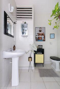 Banheiro neutro ganha vida com objetos de decoração.