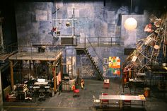 Rent's set design is very geometric. The strong influence of rectangles and angular shapes gives the environment a very industrial appeal to it. The set utilizes the use of diagonal lines on the stairs and on the very strange piece in the air on the right. The only evidently circular object on the stage is the moon,  or white orb, painted on the wall.  2/19/2013  http://www.paulclaydesign.com/1997/rent/