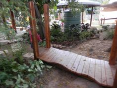 Our wavy bridge built in our play ground over our creek.  The posts have been left long at each end of the bridge so we can hang material etc over them.