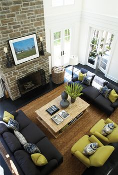 Greenery in the living room. Green furniture. Navy furniture. Stone fireplace. Reclaimed wood coffee table.