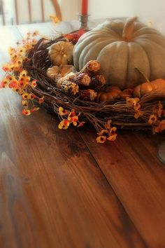 Use a wreath to frame a pumpkin/ gourd centerpiece/fall arrangement.