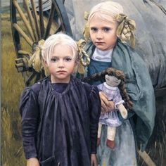 two blonde pioneer girls holding dolls and standing in front of a hand cart