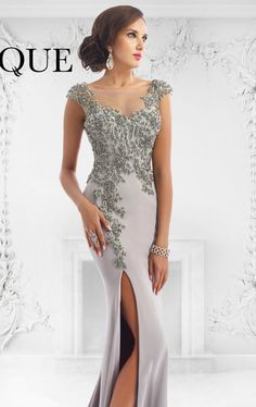 Show off your sexy side in this amazing Janique W1001 dress. This exceptional evening gown features a sheer fabric that wraps the bateu neckline and fully covers the back. Dazzling beads accentuate the fitted bodice, rounds the lower back and lead the side slit of the full length skirt.