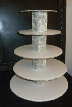 5 tier silver bling faux rhinestone white cupcake stand tower wedding cake pop display candy buffet dessert bar table serving set wedding decoration centerpiece party decor DIY  Sparkly tiered handmade cupcake stand that you will adhere together yourself. It is comprised of heavy weight cardboard cake board platforms measuring 16, 14, 12, 10, and 8 in diameter trimmed with silver rhinestone mesh with four sturdy 4 tall bling wrapped sturdy cylinder center risers making stand just over 18…