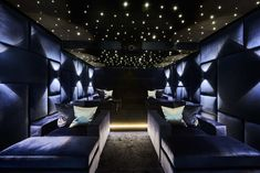 Luxurious cinema room with velvet padded walls and movie style lighting effects.