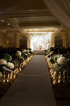 Lining the aisle with candles and flowers at indoor ceremony