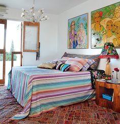 As listras e zigue-zagues tradicionais da marca Missoni, presentes na colcha e nos travesseiros, foram combinados com os quadros das artistas Verena Matzen e Isabelle Tuchband, no quarto da estilista Adriana Barra