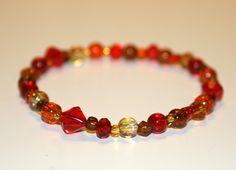 Puna-oranssi-ruskeasävyinen rannekoru.Uniikkikappale!