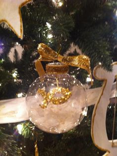 This was an original handmade ornament with a shatterproof ball you can get from any craft store.  I took off the top and added artificial snow inside.  This one has a fish symbol out of felt with glue and glitter.  I glued a piece of cording and let it hang from the top.  When I put the cap back on this helped to hold it in place.  Since the Chrismon ornaments are gold and white and the cap was silver I glued shiney gold ribbon around the edge and toped it off with a gold bow.  I loved…
