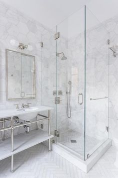Well appointed white and gray bathroom boasts a Waterworks nickel and marble double vanity accented with polished nickel vanity mirrors lit by polished nickel sconces mounted on large marble hex backsplash tiles that continue into the seamless glass shower and are fitted with a polished nickel shower kit positioned over hexagon marble shower floor tiles that also cover the floors outside the shower.