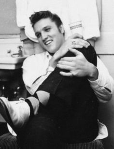 WEARY-EYED Elvis Presley relaxed in his dressing room at the Olympia Theater Friday night, while outside thou-sands of teenagers wailed and screamed. Presley staggered and swayed through three exhausting shows in his Miami debut. Copyright: Miami Herald, August 4, 1955