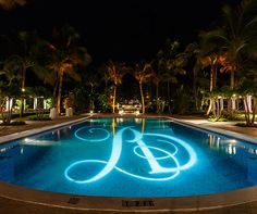 Gobo lighting allows the couple's monogram to be showcased in a beautiful aqua pool.