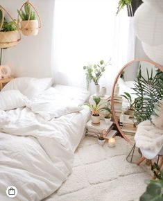 White bedroom inspiration with a boho vibe. The addition of plants and earth tones transforms the space. #whitebedroom #whitebedsheets #earthy