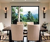 In this formal dining room a large window from Sierra Pacific frames a view of the mountains, Studio H furniture from HOLLY HUNT outfits the space. Designed by K.B. Hansel Interiors.
