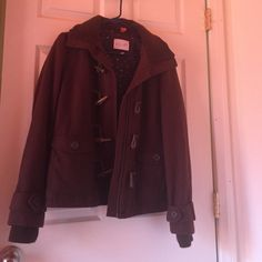 Brown Delia's coat. The beautiful brown coat has been worn but looks very nice. It had recently been dry cleaned and not worn since. It has a zipper as well as looping hooks. There is two front pockets and the cuffs have buttons. Delia's Jackets & Coats