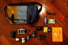 https://flic.kr/p/ko6QhS | This is my bag! | - Timbuk2 Classic Messenger Bag - Olympus E-M5 - Olympus M.Zuiko 17mm f/1.8 - Panasonic-Leica 25mm f/1.4 - Voigtlander Nokton 40mm f/1.4 - Olympus M.Zuiko 45mm f/1.8 - Olympus OM Zuiko 50mm f/1.2 - Olympus BCL-1580 - Ricoh GRDIII - Olympus mju-I - Bunch of Films (usually Kodak UltraMax) - Notebook with pens - Headphone - Deodorant to fight Thai heat - Irish Spring Soap to freshen up a bag
