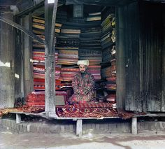 Russia Before the Revolution, in Color // 1911 A merchant at the Samarkand market displays silk, cotton and wool fabrics as well as a few traditional carpets. A framed page of the Koran hangs at the top of the stall. Color Photography, Vintage Photography, Czar Nicolau Ii, Russian Revolution, Market Displays, Imperial Russia, Portraits, Silk Road, Colour Images