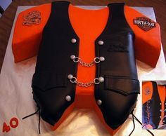 Two layer 1/2 sheet cake iced in buttercream.  Vest is chocolate fondant.  Laces, buttons, chains and decals are all gumpaste.