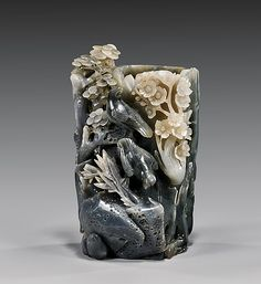 """CARVED GRAYISH-BLACK JADE BRUSHPOT Well carved, Chinese grayish-black jade brushpot; of naturalistic form, with birds and foliage in relief, with one section of white coloration H: 7 1/2"""""""