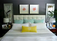 Black bedroom wall, white bed and linens, pops of color
