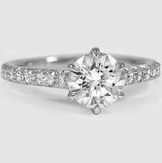 In this glamorous six prong setting, French pavé set diamonds sparkle along the band.