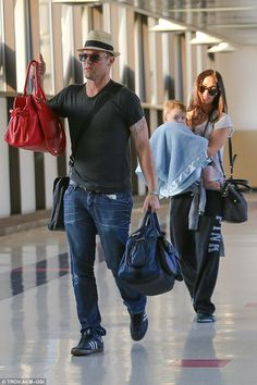 Family flight: Brian Austin Green (left) and Megan Fox (right) headed to a flight in LAX with their youngest son, Bodhi, on Friday