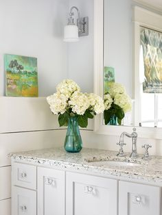 Tillman Long Interiors - bathrooms - gray walls, gray wall color, white vanity, white bathroom vanity, undermount sink, crystal hardware, quartz counter, quartz countertop, light quartz counter, light quartz countertop, polished chrome faucet, wood paneled walls, wood paneling, shiplap, shiplap paneled walls, polished  nickel sconce, landscape painting, turquoise glass vase, white hydrangeas, white mirror, white framed vanity mirror, crystal knobs,
