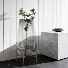 Échasse vasne fra Menu er designet av Theresa Arns. En klassisk elegant høy vase i røykfarget glass og messing. Echassé betyr stylter på fransk.
