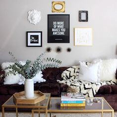 Black, white, and gold gallery wall in living room with chevron blanket, brass and glass coffee tables, and white pillows