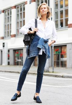 White button-down shirt, a denim jacket around the waist, skinny jeans, black backpack, and loafers.