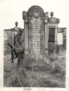 1945- U.S. 7th Army soldier takes cover by tombstone in Jewish cemetery near an Alsatian town in France.
