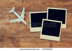 top view of blank instant photos album next to cup of coffee and airplane over wooden table. ready to put images