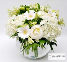 Classic all white arrangement in a bubble bowl, full of peonies, daisies, and hydrangeas!