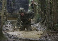 Construction Electrician Constructionman Jacob H. Raines, assigned to Naval Mobile Construction Battalion (NMCB) 3, fights through knee-high mud and water while running a six-hour endurance course at the Marine Corps Jungle Warfare Training Center (JWTC).