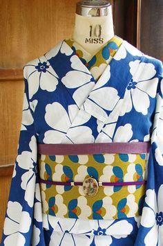 紺色に近い深みのあるスモークががかったブルーに、凛と映える白で染め出されたモダンフラワーデザインが愛らしい注染レトロ浴衣です。