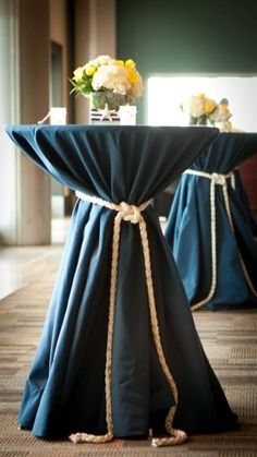 These cocktail tables would be perfect for a nautical theme wedding. Navy blue table linens with thick rope knotted around the draping cloth.
