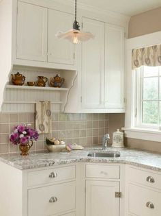 Honed granite countertops, beige tile, and a Mackintosh-print valance and tea towel add subtle layers of color to a Colonial Revival kitchen...