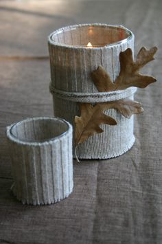 The cuff of an old sweater is cut and sewn to fit a glass candle holder – an oak leaf adds a natural element.