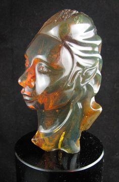 Enchanting elfin fairy woman bust carved in yellow Mexican amber, left half raw with incredible color play