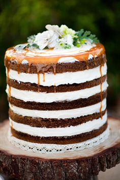 Naked cake with lots of frosting and caramel topping with a few simple flowers, garden party cake would be nice
