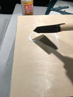 Applying glue to a wooden board before applying a photo canvas