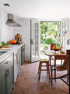 An antique wooden table and unique chairs are fitting choices for a cottage kitchen filled with crea. Kitchen Flooring Trends, Kitchen Flooring, Small Kitchen, Eat In Kitchen Table, Kitchen Design Small, Kitchen Remodel, Kitchen Renovation, Farmhouse Kitchen Decor, Brick Kitchen