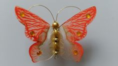 Magnetic butterfly made using recycled flat plastic, acrylic paints, gems to bling and bead and wire to make the body.