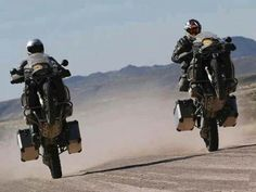 A pair of adventure riders using TKC 80s from Continental take the opportunity to pull a wheelie with no other vehicles in sight on this desert track