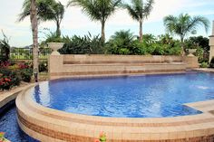 A beautiful pool design by Ocean Quest Pools featuring a custom water feature topped by custom  Authentic Durango Veracruz marble limestone coping.