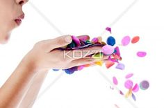 female blowing confetti from her hands. - Close-up shot of a woman blowing colorful confetti from her hands against white background.