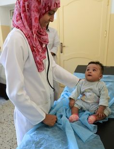 A doctor treats the child of a family fleeing from the fighting in Sirte at a medical center in Herawa, 70 km (43 miles) east of Sirte, October 1, 2011.