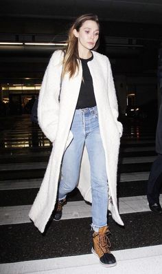 Elizabeth Olsen was recently spotted at LAX airport sporting a long textured coat with a simple black top, jeans and winter boots.