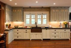 Love the farmhouse sink, light rails, and three contrasting cabinet colors.